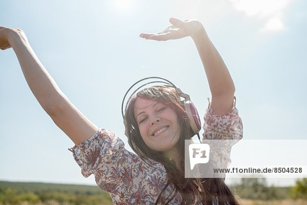 Porträt einer mittleren erwachsenen Frau  die im Feld tanzt und Kopfhörer mit erhobenen Armen trägt. Porträt einer mittleren erwachsenen Frau, die im Feld tanzt und Kopfhörer mit erhobenen Armen trägt.