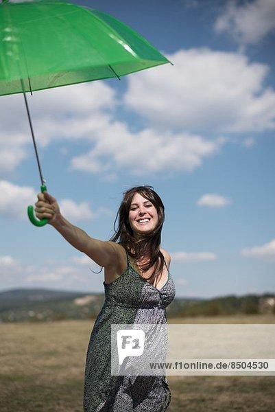 Mittlere erwachsene Frau mit grünem Regenschirm