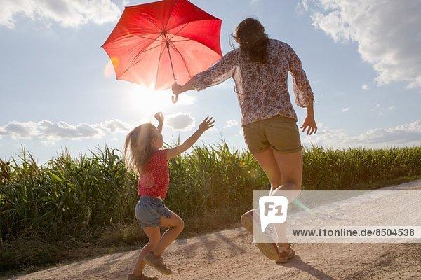 Mutter und Tochter gehen mit rotem Regenschirm durchs Feld. Mutter und Tochter gehen mit rotem Regenschirm durchs Feld.