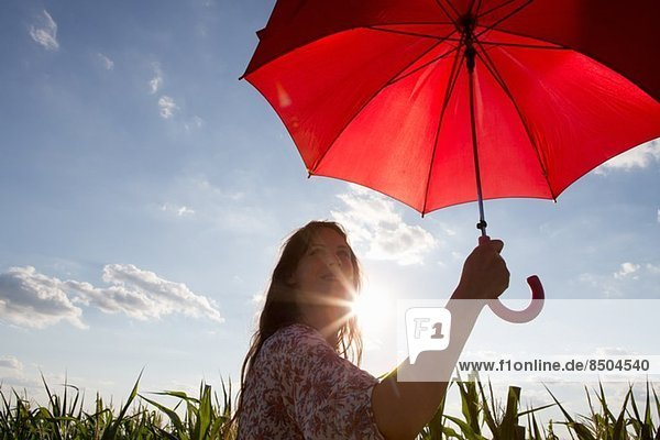 Frau stehend mit rotem Regenschirm Frau stehend mit rotem Regenschirm