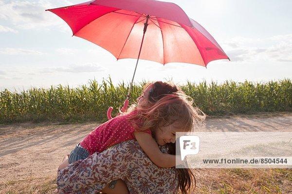 Mutter und Tochter umarmen sich unter rotem Regenschirm Mutter und Tochter umarmen sich unter rotem Regenschirm