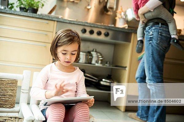 Mädchen mit digitalem Tablett in der Küche