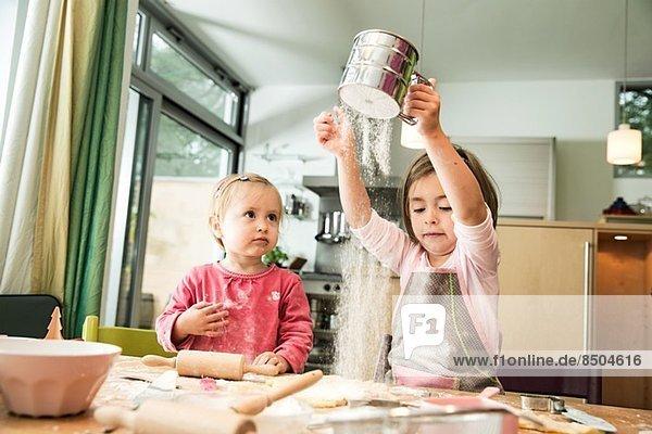Mädchen sieben Mehl in der Küche