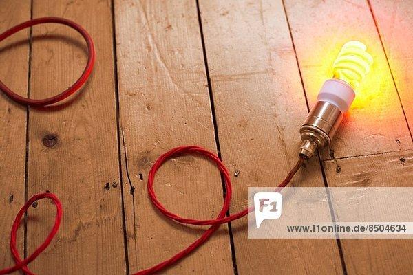 Stilleben von Energiesparlampen auf Holzdielen