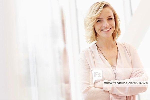 Porträt einer mittleren erwachsenen Frau mit gekreuzten Armen