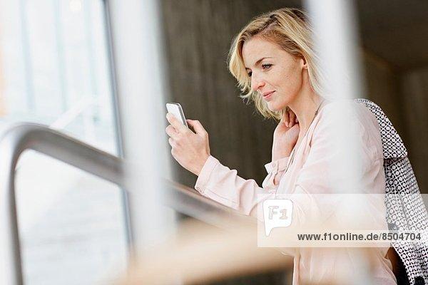 Geschäftsfrau mit Handy im Bürogebäude