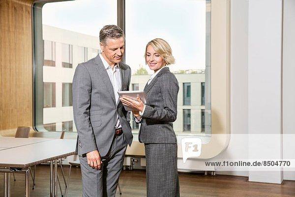 Geschäftsleute  die im Konferenzraum stehen  mit digitalem Tablett