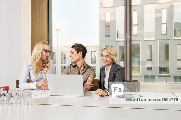 Geschäftsfrauen sitzen am Konferenztisch mit Laptop