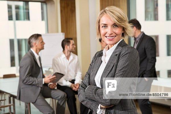 Geschäftsfrau steht vor Kollegen