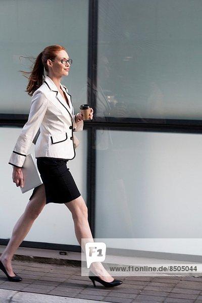 Geschäftsfrau zu Fuß  mit heißem Getränk und digitalem Tablett
