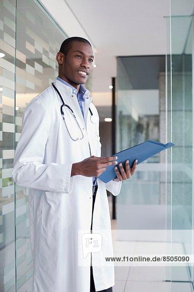 Doctor standing in hospital corridor holding paperwork