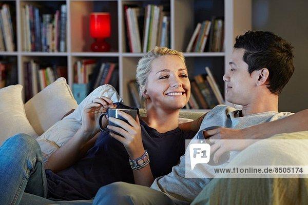 Junges Paar auf dem Sofa sitzend mit heißen Getränken