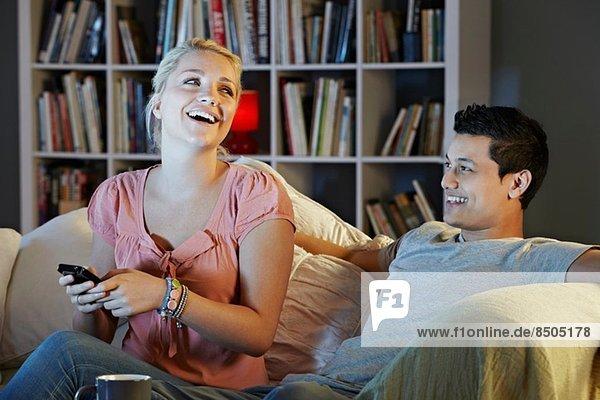Junges Paar beim Fernsehen  lachend