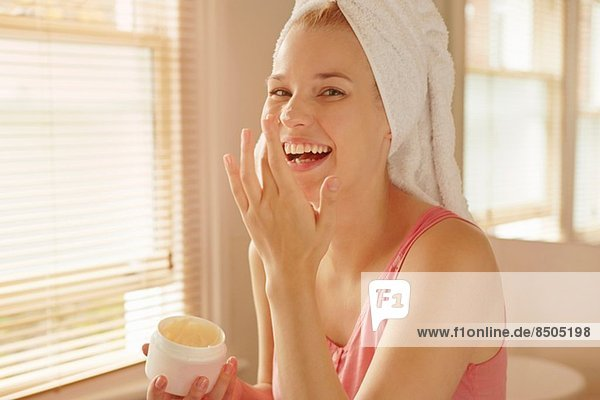 Junge Frau im Bad mit Gesichtscreme