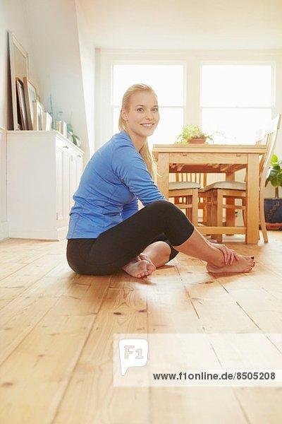 Junge Frau in Sportkleidung auf dem Boden sitzend