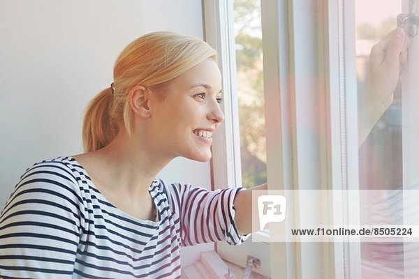 Young woman opening window