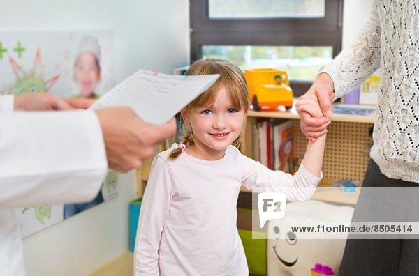Mädchen hält Händchen mit Mutter beim Zahnarzt