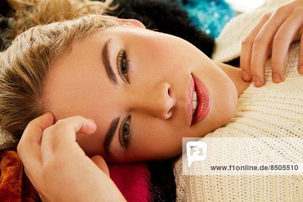 Nahaufnahme des Porträts einer jungen Frau  die auf einer pelzigen Decke liegt.