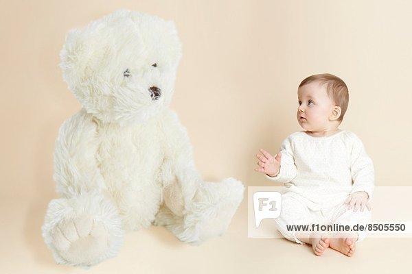 Studio-Porträt des Mädchens neben dem riesigen Teddybären