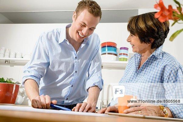 Erwachsener Enkel und Großmutter beim Betrachten des digitalen Tabletts