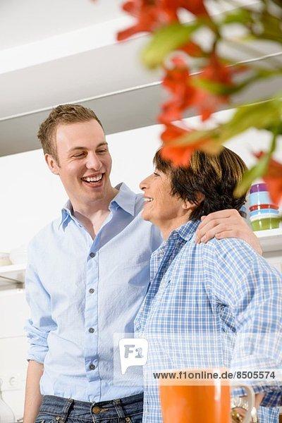 Erwachsener Enkel und Großmutter in der Küche