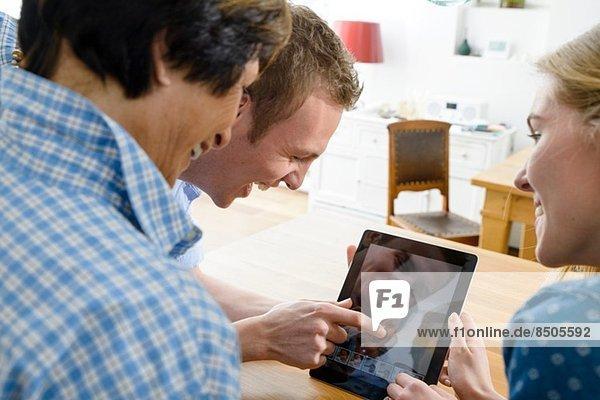 Großmutter und erwachsene Enkelkinder mit Verzerrung auf digitalem Tablett
