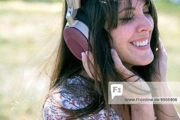 Mittlere erwachsene Frau mit Kopfhörer und geschlossenen Augen Mittlere erwachsene Frau mit Kopfhörer und geschlossenen Augen