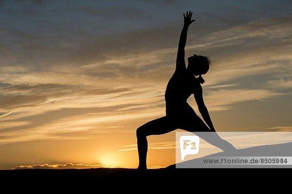 Silhouette of young woman doing yoga  Moab  Utah  USA