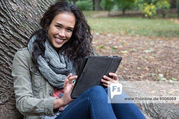 Junge Frau  die sich mit einem digitalen Tablett an den Baum lehnt