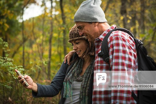 Mature couple taking self portrait photograph on smartphone in forest