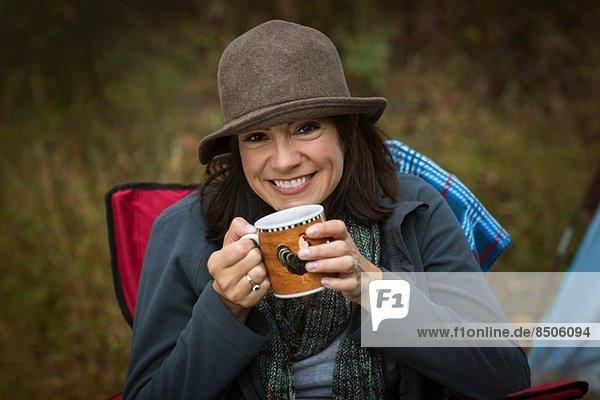 Reife Frau sitzt auf einem Campingstuhl und trinkt ein heißes Getränk.