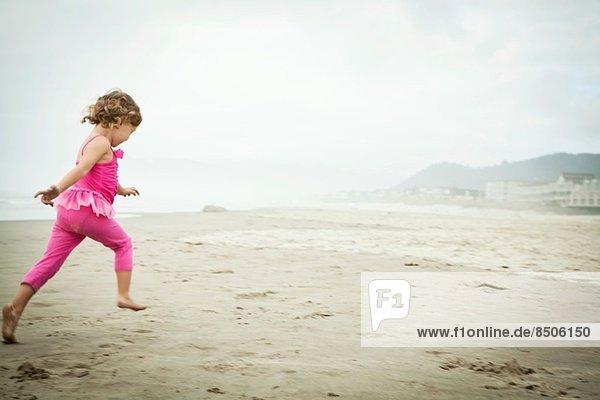 Weibliches Kleinkind beim Laufen am Strand