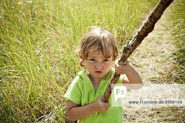 Porträt eines weiblichen Kleinkindes mit langem Stock