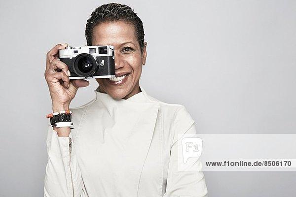 Studio-Porträt einer fröhlichen reifen Frau  die die Kamera hochhält