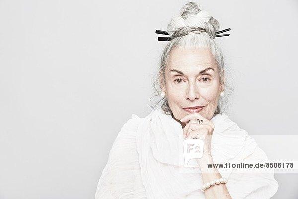 Studio-Porträt einer anspruchsvollen Seniorin mit Hand am Kinn