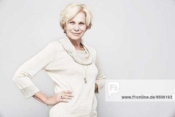 Studio-Porträt einer älteren Frau mit Händen auf der Hüfte