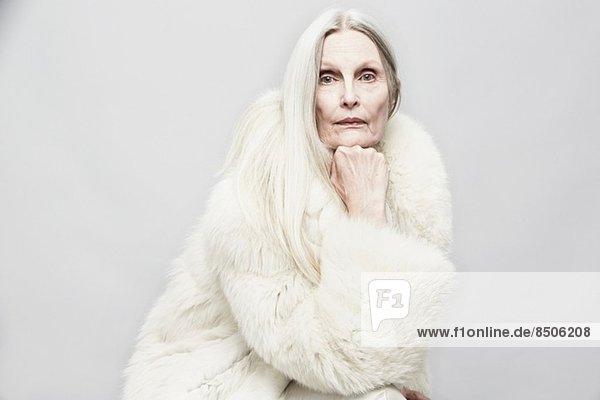 Studio-Porträt einer älteren Frau mit Hand am Kinn
