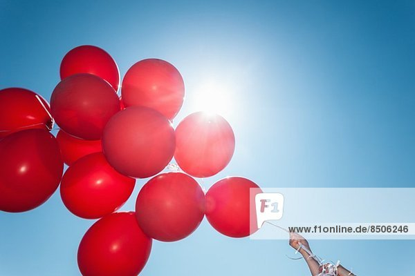Hands holding bunch of red balloons against blue sky, Hands holding bunch of red balloons against blue sky