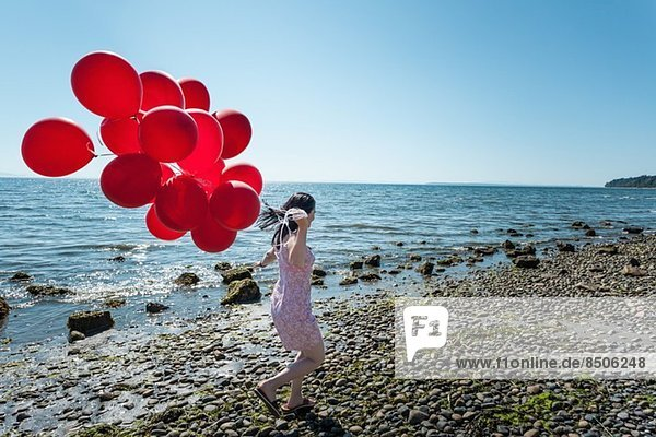 Mature woman pulling bunch of balloons, Mature woman pulling bunch of balloons