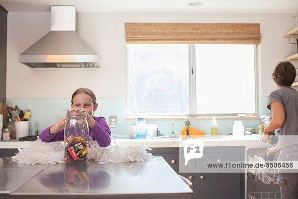 Tochter bekommt heimlich Keks aus dem Keksfass