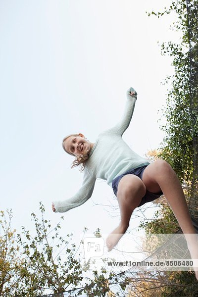 Mädchen springen in der Luft auf Gartentrampolin