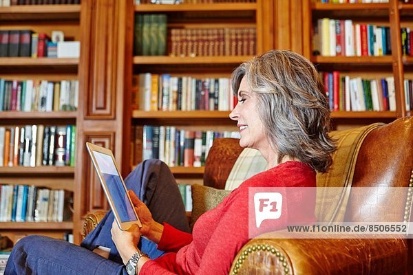 Reife Frau im Heimstudium mit digitalem Tablett