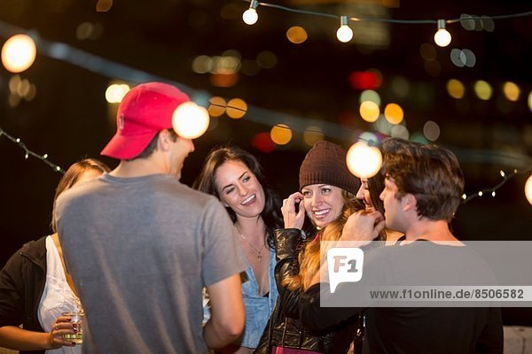 Young adult friends having fun at rooftop party