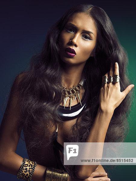 Frau mit langen dunklen Haaren und Schmuck