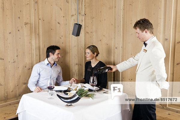 Mann und Frau in einem Restaurant werden vom Kellner bedient  Regensburg  Bayern  Deutschland Mann und Frau in einem Restaurant werden vom Kellner bedient, Regensburg, Bayern, Deutschland