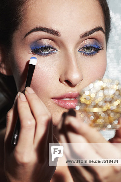 Close-up of beautiful young woman applying blue eyeshadow