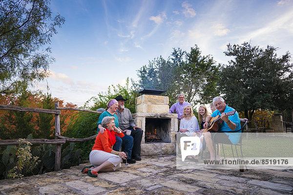 USA  Texas  Gruppe von Leuten mit Gitarre am Kamin sitzend