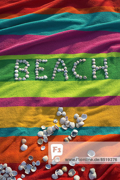 The word 'beach' formed by shells lying on a multicolored bath towel