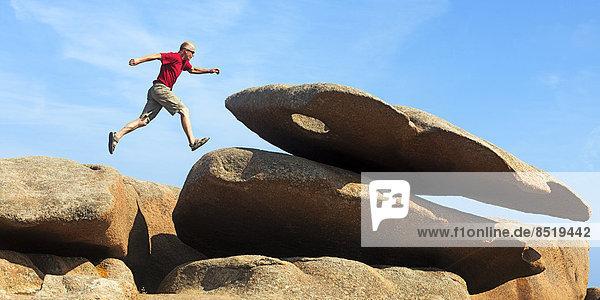 Frankreich  Bretagne  Tregastel  Mann auf Felsen springend