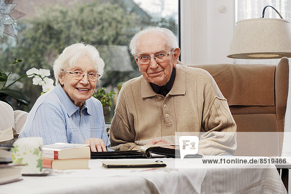 Senior couple watching old photographs at home